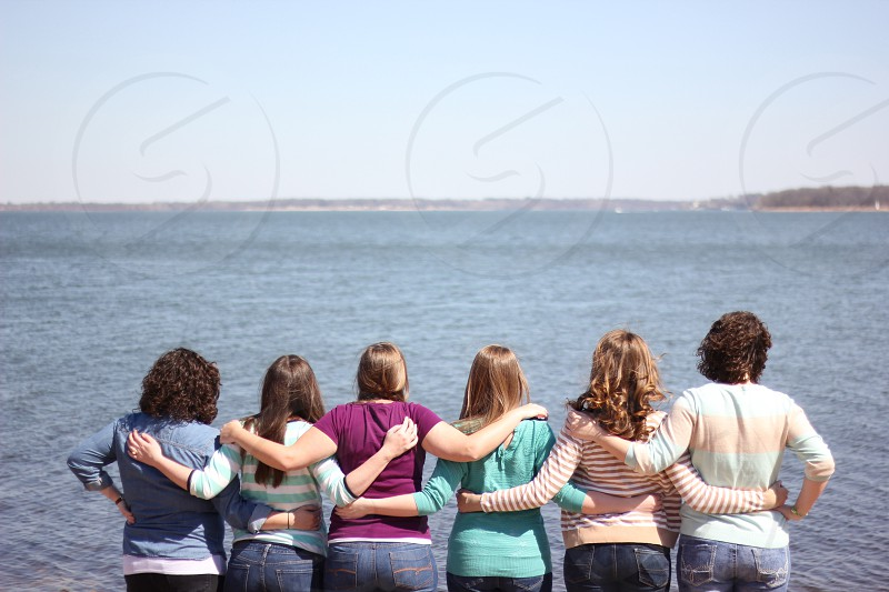 6 women holding each other facing sea overlooking island under clear sky during daytime photo