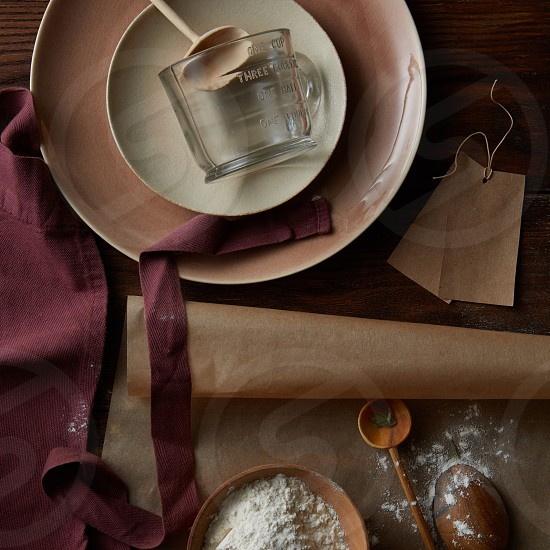 Kitchen accessories with a plate bakery paper and apron on a wooden background with flour in a bowl for baking pie or pancake flat lay photo