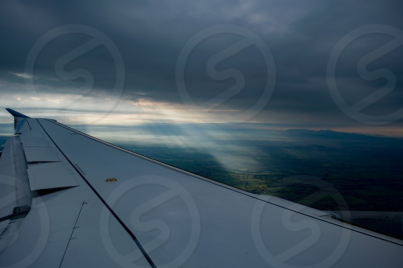 An aerial view of Italian landscape with airplane wing and god rays falling from dramatic clouds at the background photo