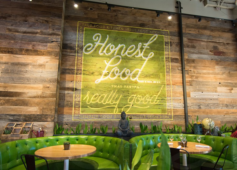 honest food signage above green leather bench photo