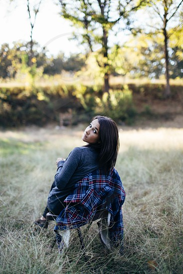 woman in field wearing blue denim shirt with blue and red plaid flannel shirt photo