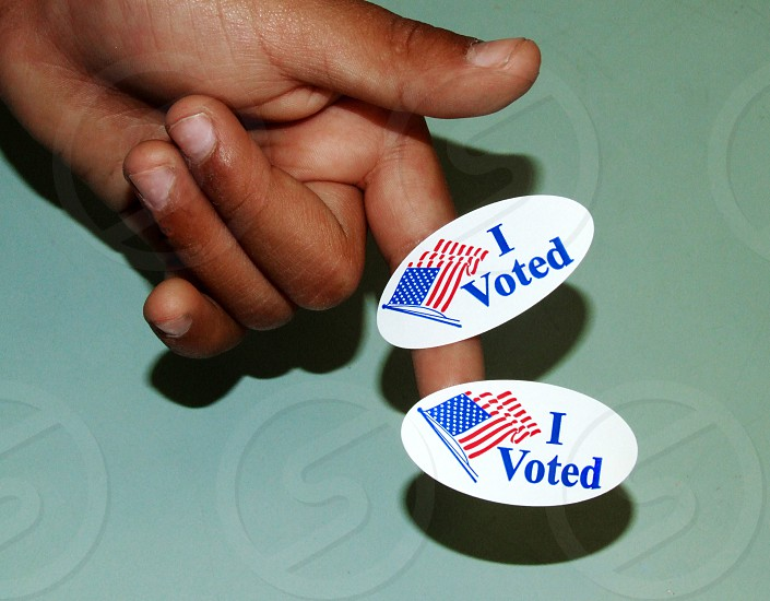 """A child's hand is seen with two """"I Voted"""" stickers on his pointing index finger photo"""