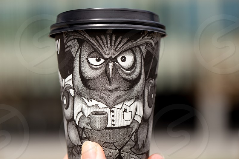 Black paper disposable coffee cup with a drawn owl in hand on a blurred background outdoor photo