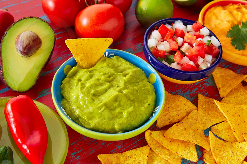 Mexican food nachos guacamole pico de gallo and dipping cheddar cheese photo