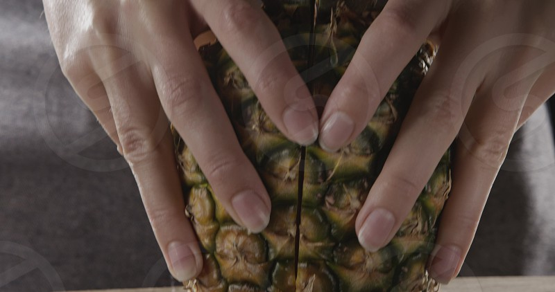 Close up viev od two halves of ripe fresh natural organic tropical fruit pineapple in a girl's hands on a cutting wooden board. Dolly out slow motion 4K UHD video 3840 2160p. photo