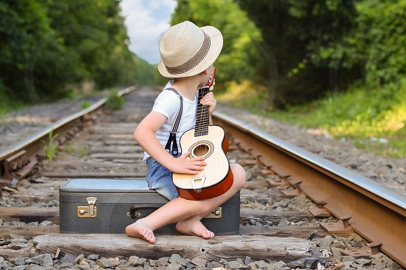 Boy playing guitar on tracks while sitting on a suitcase and waiting for a train in the sun during the summer. photo