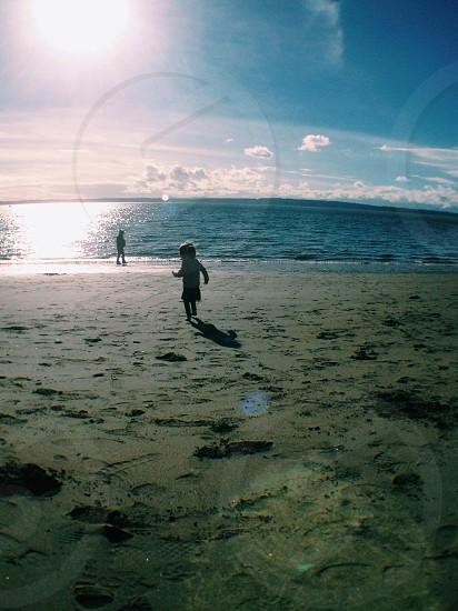 girl running on sand near seawater photo