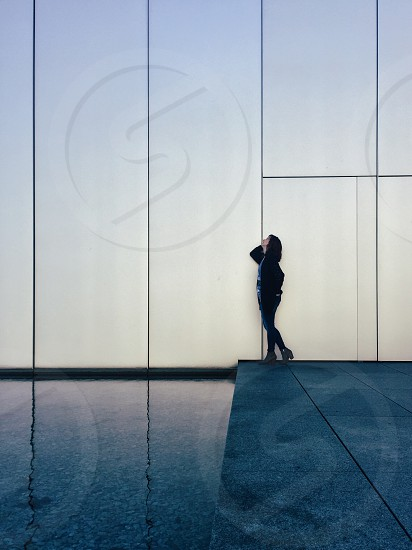 woman with black short hair wearing black jacket and pants standing near white wall during daytime photo