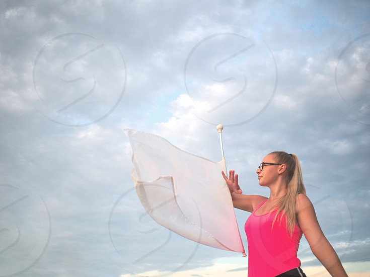 Bespectacled Blonde Teen Majorette Girl with White Flag Outdoors photo
