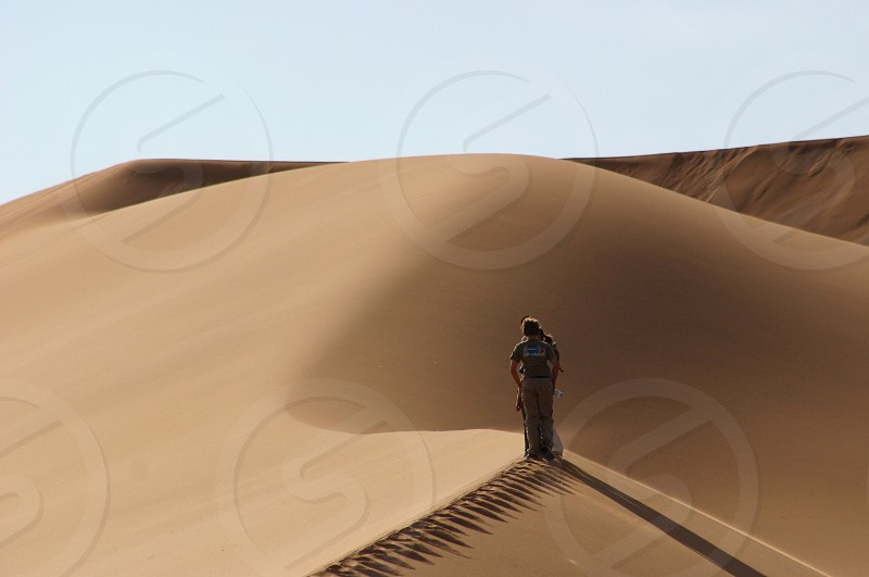 woman in grey t shirt walking on desert photo