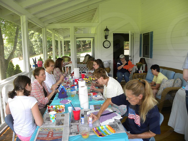 Valley ladies having fun painting birdhouses dragon flies or butterflies.  photo