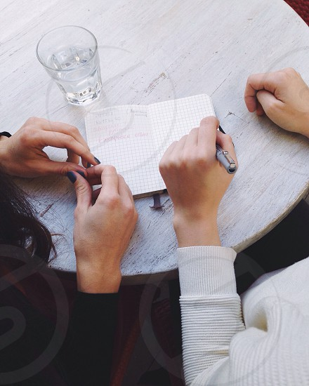 person writing on booklet on table beside another woman photo
