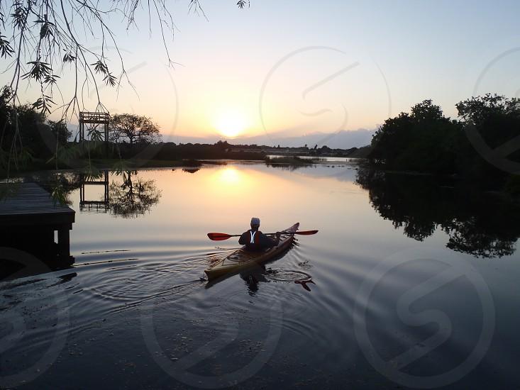 kayaking into the sun setting over the lake photo