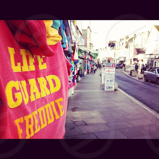 pink and yellow life guard freddie shirt at stand on street photo