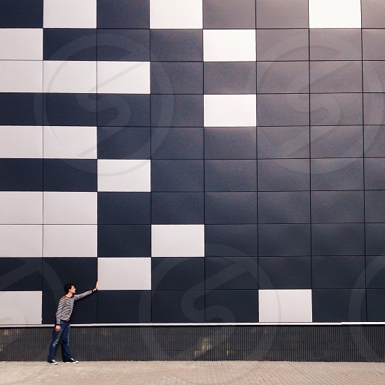 man in grey sweater touching white wall tile photo