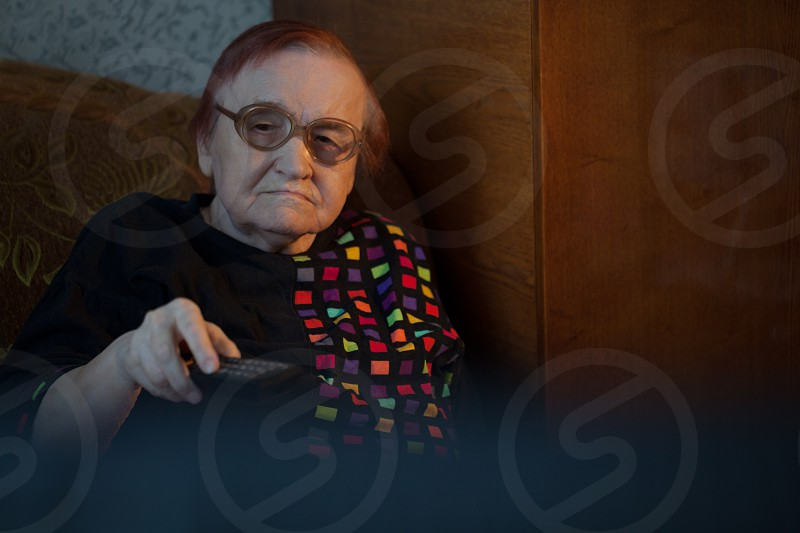 Elderly woman in glasses sitting on the sofa and changing channels on TV with remote control photo