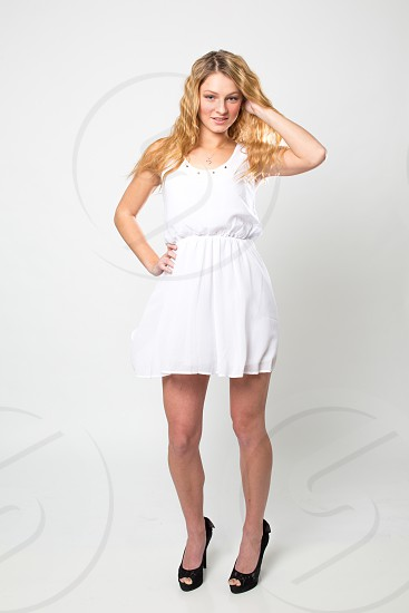 Experienced model in a white dress shooting in studio with a solid white background and long hair. photo
