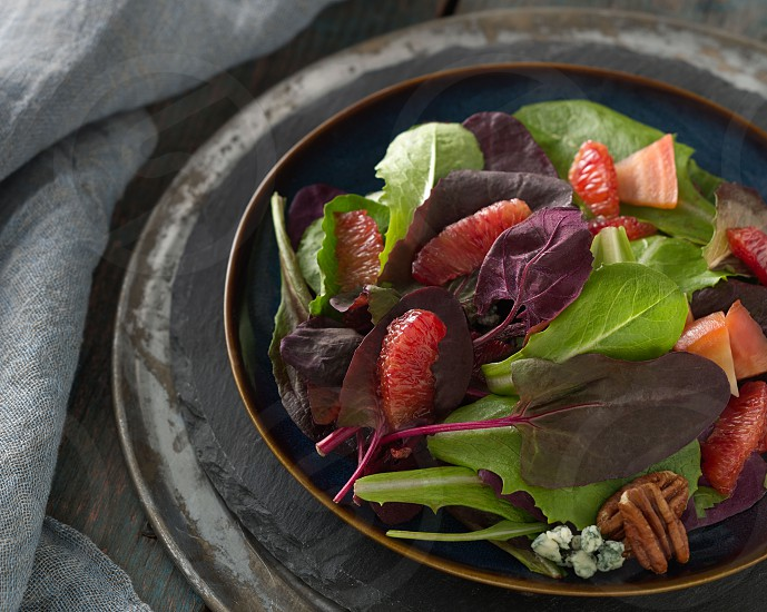 pecan mandarins and bleu cheese green salad on a round plate photo