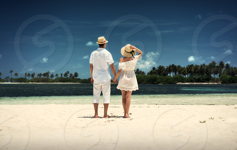 A guy and a girl in white clothes on the shore of the island. Maldives. White sand. Guraidhoo. Vacation. photo