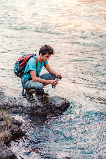 Young wanderer takes pure water from a river into mug. He is sitting on a rock over the river rests during a hike spends a vacation on wandering with backpack he is wearing sport summer clothes photo