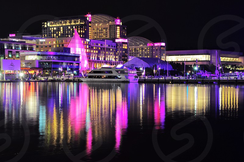 photo of a architectural building with purple lights near body of water with white yacht during nighttime photo