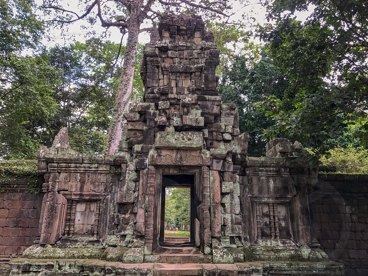 Outdoor day colour landscape horizontal Angkor Angkor National Park Siem Reap Cambodia Asia Asian east eastern ancient holy spiritual Khmer dynasty monument sky blue white clouds summer travel tourism tourist wanderlust stone carved ornate elaborate figure figures temple grounds ruin ruined trees door doorway photo
