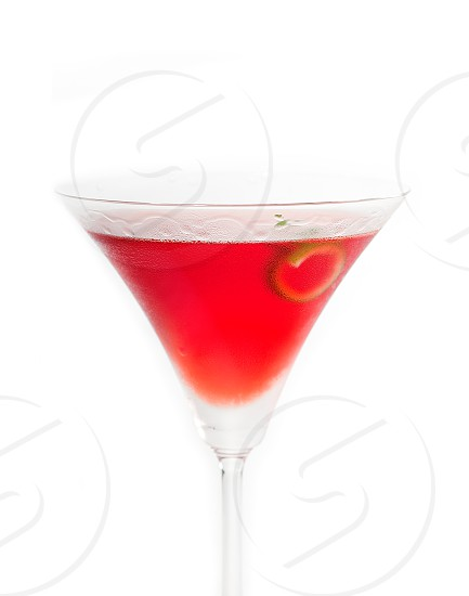 cosmopolitan drink cocktail straight up on martini cup with lime peel isolated on white background photo