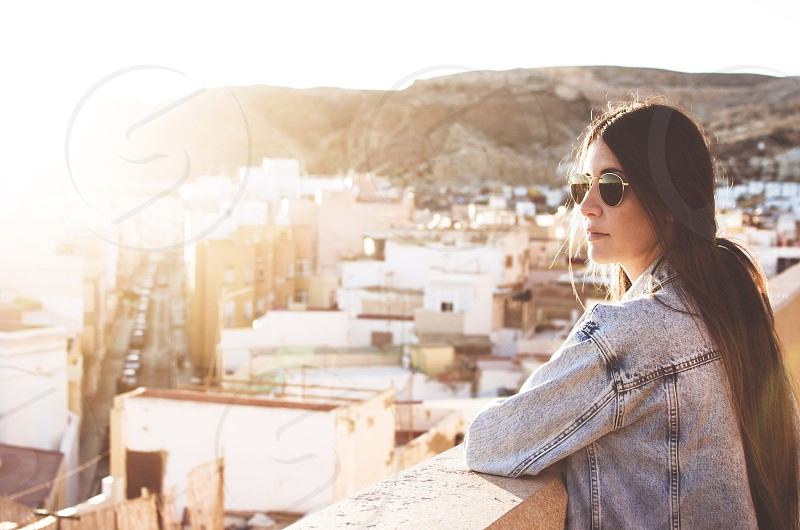 beautiful young woman with sunglasses is in a viewpoint in the city looking at the horizon at golden hour photo