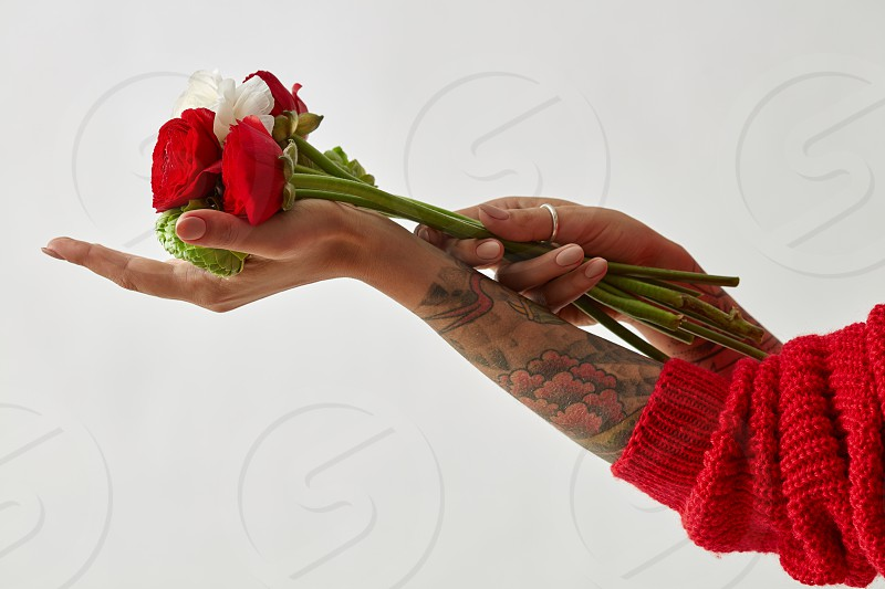 a bouquet of red white and green flowers in the hands of a girl with a tattoo on her hands. Mother's Day. Valentine's Day. photo