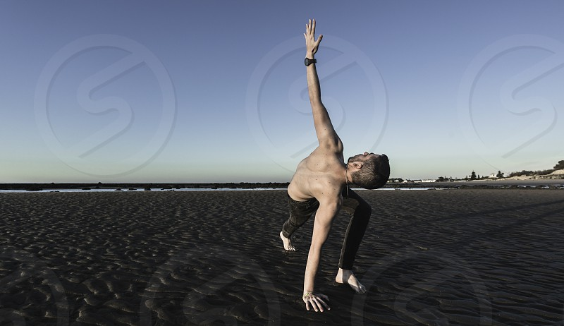 Young man doing yoga on the sand beach of Sanlucar de Barrameda when the tide is low photo
