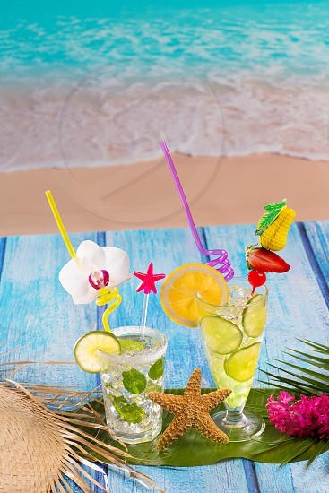 Mojito and lemon lime Cocktails in tropical blue wood at turquoise Caribbean beach photo