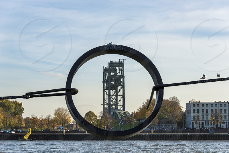 an old railroad bridge in rotterdam seen througt a metal circle over the water the meuse photo