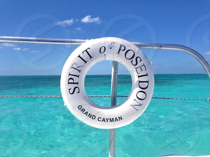 spirit of poseidon grand cayman floater on stainless steel handle near blue sea during daytime photo