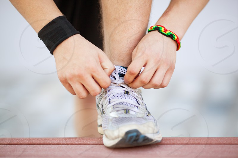 Close-up shot of man tying running shoes with foot on the bench. Getting ready before jogging. Going in for sports healthy lifestyle photo