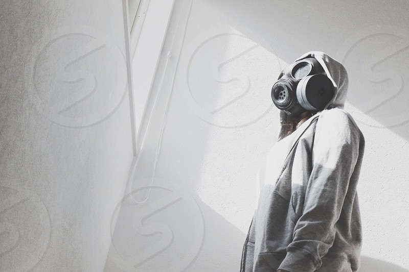 grayscale photo of person in gas mask and hoodie facing window photo