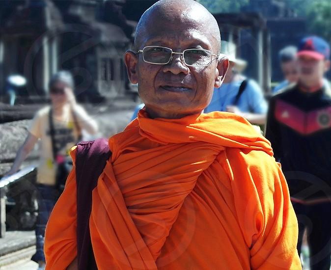 man in orange top wearing eyeglasses photo