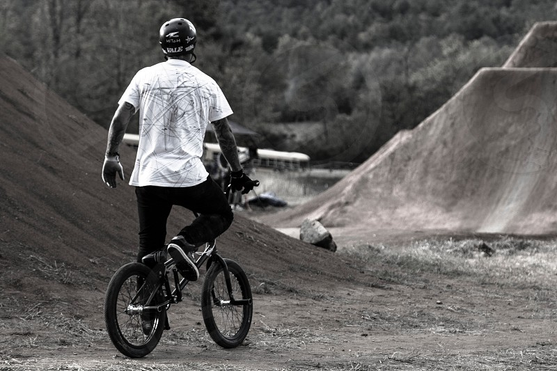 grayscale photograph of man riding BMX bike near trees photo