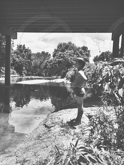 childhood boy water bridge creek black and white profile america south american south texas central texas summer photo