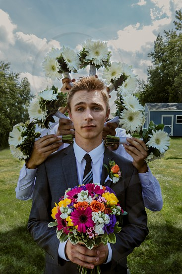 man in grey suit holding bouquet photo