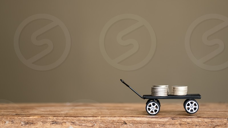 silver money coin delivery on black toy wagon on wooden table copy space photo