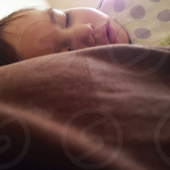 baby sleeping on brown blanketed bed photo