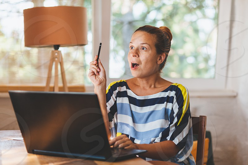 Young woman working on laptop in home office photo