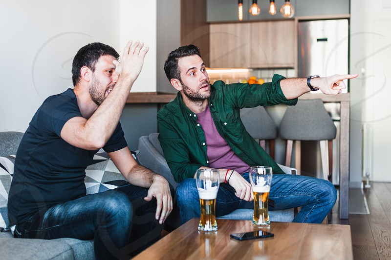 Two guys drinking beer watching football on TV photo