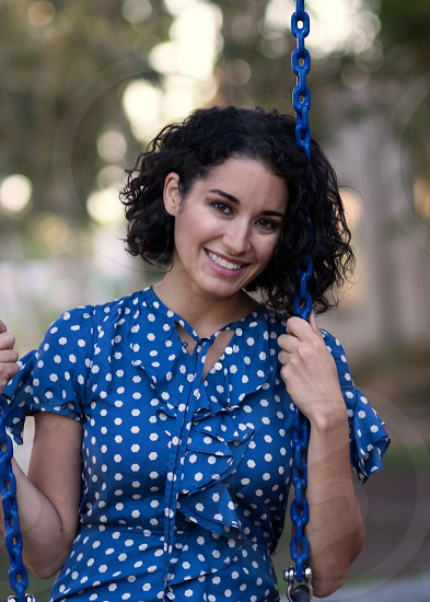 pretty curly brunette with a beautiful smile in a blue polka dot dress on a blue swing at West Hollywood park photo