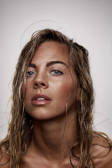 Female model with wet hair shot on white background in studio photo