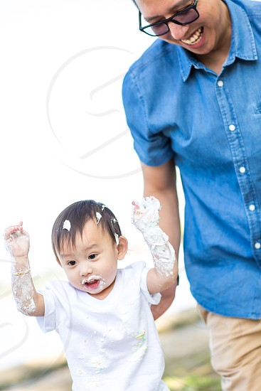 Asian Baby's first Birthday Cake with dad  getting messy photo