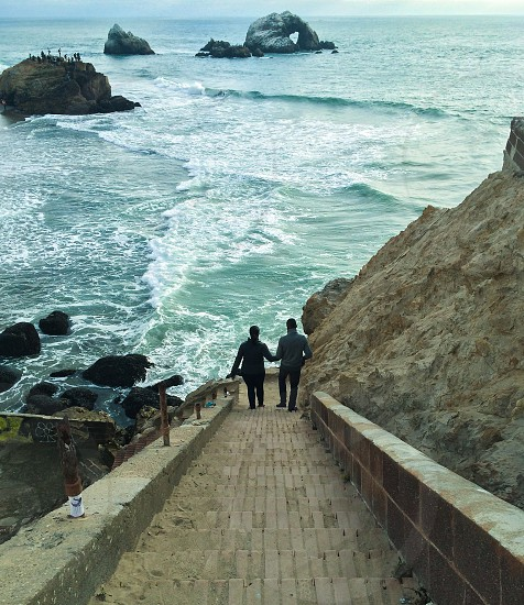 couple walling down beach stairs photo