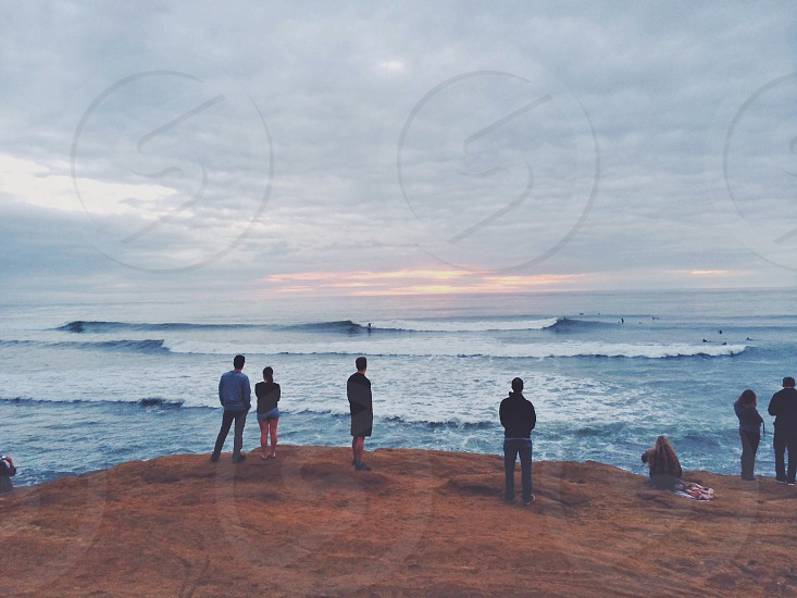 people standing on brown floor by blue white water waves photo