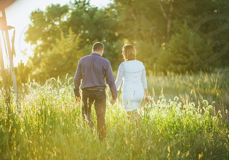 Couple walking holding hands country field sunset engagement. photo