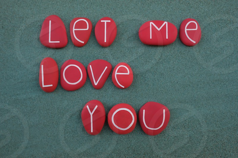 Creative message let me love you composed with red colored and carved stone letters over green sand photo